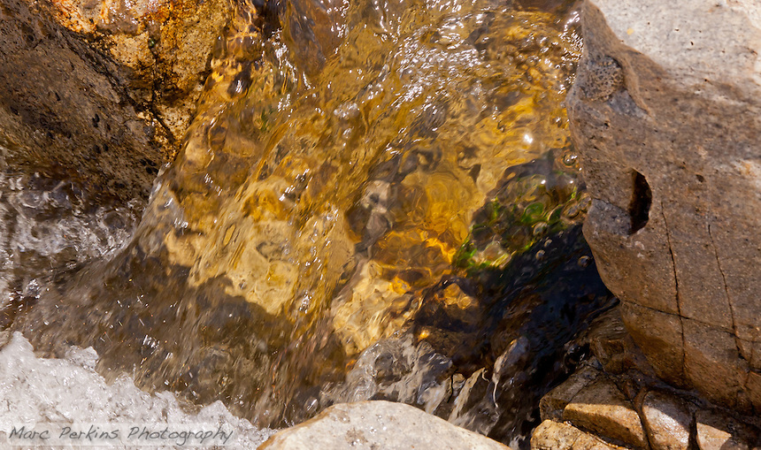 Water pours through an opening in San Juan Falls (Cleveland National Forest), looking like a huge rippling sheet of glass (at least to me).  I love how the water distorts the streambed and rocks behind it :)