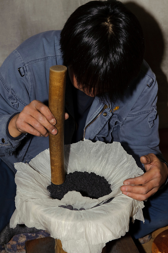 "A worker fills a firework with gunpowder, Katakai Fireworks Co., Ltd, Katakai, Japan, April 6, 2009. The company makes the world's largest firework, a 120cm round shell called a ""yonshakudama""."
