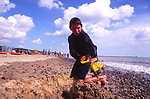 AMHJE7 Boy digging sand Walberswick beach Suffolk England