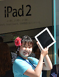 April 28, 2011, Tokyo, Japan - A Japanese women show off their iPad2 in front of Apple Store in Tokyo Ginza shopping district as the tablet computers go on sale in Japan at long last on Thursday, April 28, 2011. iPad2 was originally set to go on sale on March 25 but was postponed as the country grapples with the earthquake and tsunami devastation. (Photo by Natsuki Sakai/AFLO) [3615] -mis-