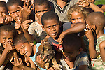 Warrior Village, Taveuni, Fiji; local children pose for pictures on the edge of the rugby field in the Warrior Village at the south end of the island
