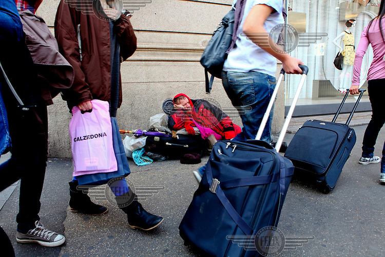 Passengers, on their way to the train station, pass a homeless man sleeping on the pavement.