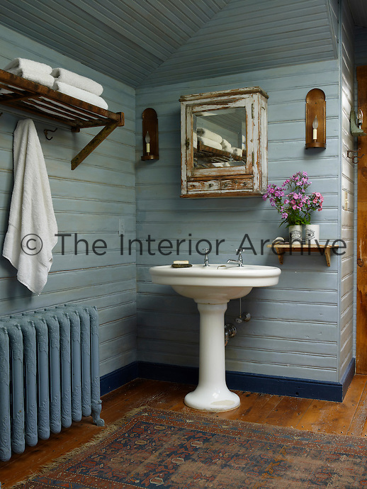 This blue-painted bathroom features a Victorian-style pedestal wash basin