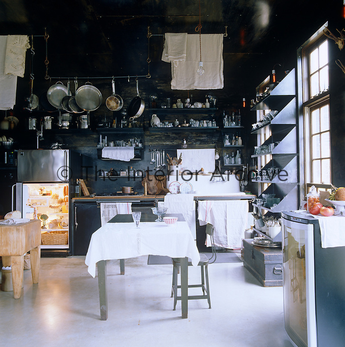 Shelving storing glassware and pots and pans covers the  steel walls of the kitchen-diner