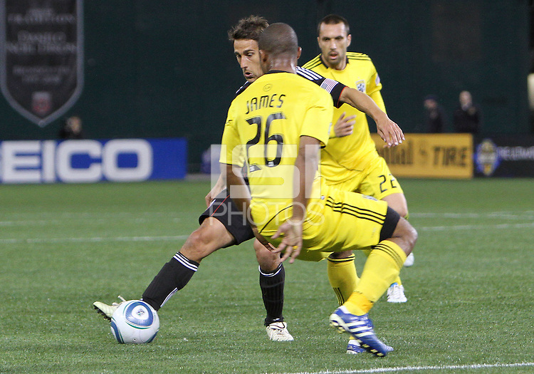 Josh Wolfe#16 of D.C. United sends a pass away from Julius James#26 of the Columbus Crew during the opening match of the 2011 season at RFK Stadium, in Washington D.C. on March 19 2011.D.C. United won 3-1.