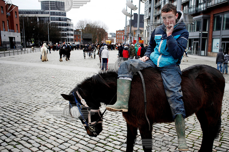A boy sits on a horse smoking a cigarette at Smithfield horse market in central Dublin. This traditional market has now became a place for people from the poor neighbourhoods who cannot afford to look after their horses anymore to trade them, sometimes for as little as 80 Euros. The horses are often mistreated.