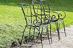 Three green iron chairs in Bellagio, Italy on Lake Como.