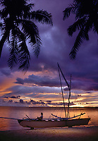 Girl Sitting on Outrigger Canoe Sunset at Bora Bora Lagoon Bora Bora French Polynesia.