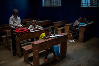 MONROVIA, LIBERIA - FEBRUARY 18: James Nyema, 9, sits and writes on the third day of school, after the 2nd grade teacher didn't show up on the third consecutive day, at the C.D.B. King Elementary School on February 18, 2015 in Monrovia, Liberia. Though Ebola cases have receded into the single digits in Liberia, lingering fear and a depressed economy have dampened the turnout at schools. Many have yet to reopen, having failed to meet the minimum requirements put in place to prevent the transmission of the virus. Many of those that have reopened – like C.D.B. King, which, though located in the center of the capital, lacks electricity and running water, and has only a few toilet stalls for a student population that numbered 1,000 before Ebola — are struggling.<br /> Daniel Berehulak for The New York Times