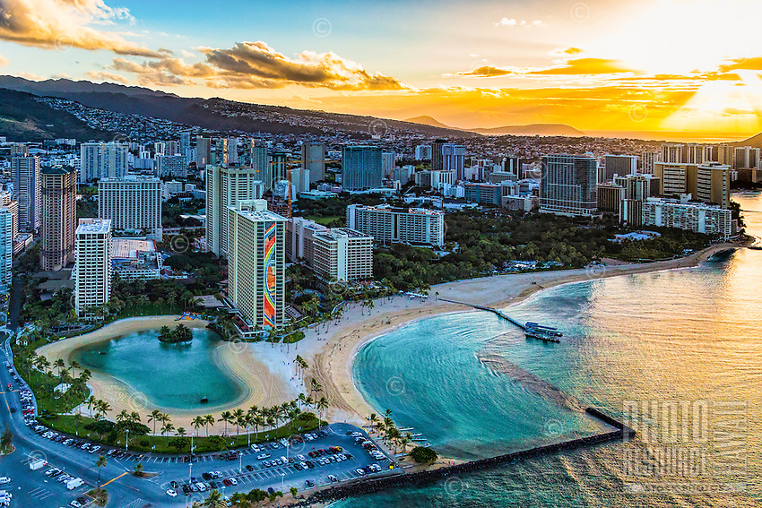 A golden morning sun rises over O'ahu, with the Hilton's Duke Kahanamoku Lagoon on the left and the Duke Kahanamoku Beach on the right. <br /> <br /> Aerial sunrise behind the Hilton Hawaiian.