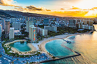 A golden morning sun rises over O'ahu, with the Hilton's Duke Kahanamoku Lagoon on the left and the Duke Kahanamoku Beach on the right. <br />