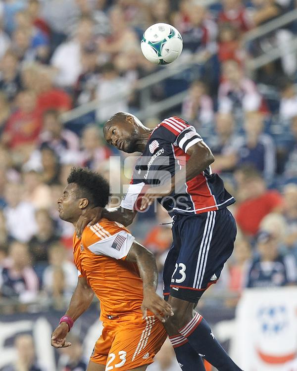 Houston Dynamo midfielder Giles Barnes (23) and New England Revolution defender Jose Goncalves (23) battle for head ball.  In a Major League Soccer (MLS) match, Houston Dynamo (orange) defeated the New England Revolution (blue), 2-1, at Gillette Stadium on July 13, 2013.