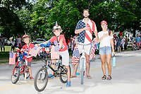A family with many American flags stands at attention during the National Anthem after the 4th of July Parade in Amherst, New Hampshire, on Thu., July 4, 2019.