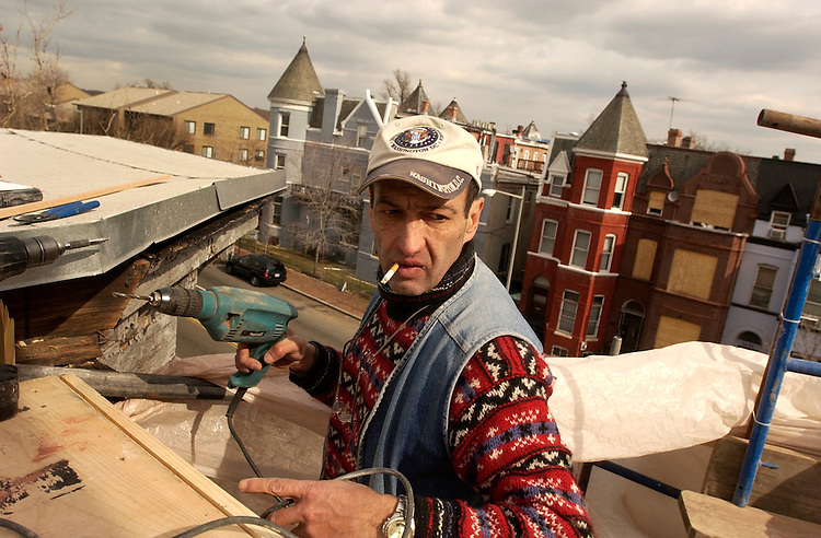 Irakli Chachanicze drills holes in preparing to install molding around the roof of a townhouse on 6th Street, NW.  The house will be featured on This Old House.