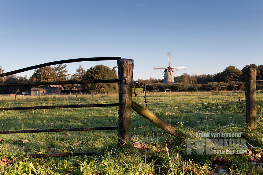 Rural Dutch Landscape with farm fence and windmill.
