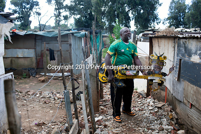JOHANNESBURG, SOUTH AFRICA - MAY 10: Alfred Baloyi, an artist, and the founder of the Makarapa Helmet stands outside his old studio wearing one of his older creations, a guitar makarapa in a squatter camp in Primrose, Johannesburg, South Africa. Mr. Baloyi, and a diehard Kaizer Chiefs soccer fan, started to make these hats in 1979. Initially he asked a friend who worked at a construction site for a helmet, as he wanted to protect himself from missiles at games. He later started to paint it, and later started to make this different figures hand cut out from the helmet. During the years he has made many different artistic hats that are on display in his studio in a shack in Primrose, Johannesburg. He later gave up his job as a washer of busses. From his small workshop in a squatter camp in Primrose south east of Johannesburg he recently made partner with an investor and have a brand new factory with about fifty people employed to make the hats. (Photo by Per-Anders Pettersson/Getty Images)