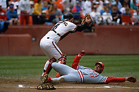 SAN FRANCISCO, CA - Kirt Manwaring of the San Francisco Giants is late applying a tag at home plate as Cincinnati Reds base runner Barry Larkin slides home safely during a game in 1992 at Candlestick Park in San Francisco, California. (Photo by Brad Mangin)