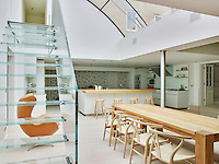 Glass stairs and a large skylight allow the light to infuse the kitchen dining area of this converted manor house