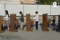 Four children (6-13) playing pianos, side view (Licence this image exclusively with Getty: http://www.gettyimages.com/detail/200482298-001 )