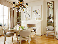 A stylish dining room furnished in neutral tones and wooden floor. A gilt chandelier hangs above a circular dining table laid for lunch.