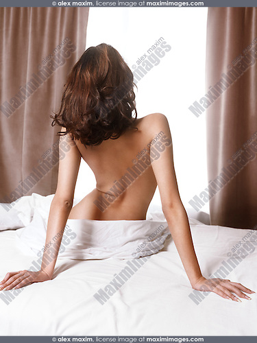 Back of a young woman sitting naked on a bed in front of a brightly lit window