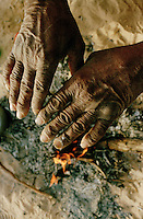 A man warms his hands over an open fire in the south of Tunisia