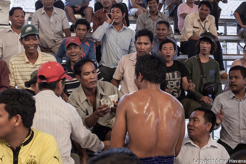 """SIEM REAP, CAMBODIA. A spectator gives some dollars to one of the fighters after he won his fight in the new Siem Reap arena in Cambodia. Cambodians boxers were traditionally paid by the crowd: if the crowd appreciated the boxer's efforts, they would reward him with alcohol, food or cash. This practice still continues today but, in line with western practice, bouts pay official fees. A new Cambodian boxer can earn US$25 per fight. More experienced kick boxers with more than a dozen fights can earn up to $75. """"Brand name"""" kickboxers can earn over $100 a fight. Special purse fights will pay up to $250 with the purse contributed by a corporate sponsor. Pradal Serey or Kun Khmer -free fighting- is an unarmed martial art from Cambodia. Compared to other forms of Southeast Asian kickboxing, Kun Khmer emphasises more elusive and shifty fighting stances. The Cambodian style tends to utilise more elbows than that of other regions. Evidence shows that a style resembling pradal serey existed in the 9th century, leading the Khmer to believe all Southeast Asian forms of kickboxing started with the early Mon-Khmer people. They maintain that Pradal Serey has influenced much of the basis of Muay Thai. During the Khmer Rouge genocide, traditional martial arts were banned and many boxers were executed or worked to death, which nearly caused the death of pradal serey. Nowadays, Kun Khmer is making a strong comeback in Cambodia, with fighters attempting to market their style of boxing at the same caliber of Muay Thai. Photography: ©Omar Havana"""