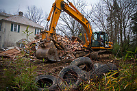 Workmen demolish one of the buildings at the Japanese Tea House in Westerville, OH. The abandoned buildings and shrine are being demolished after the buildings fell into disrepair when it's original owners died and new owner failed to maintain its condition. The property was purchased by the city  which has yet to decide how to use the soon to be cleared land.