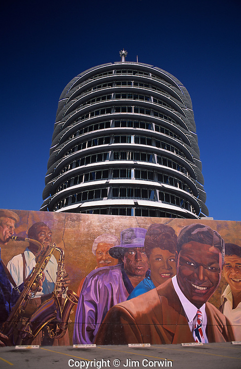 Capitol Records building with musicians mural in foreground parking lot, Hollywood, Los angeles, California USA