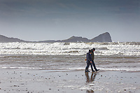 Pictured: People walk on the beach with Worm's Head in the backgorund. Tuesday 18 February 2020<br /> Re: General view of Rhossili in the Gower Peninsula near Swansea, Wales, UK.