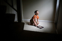 "Jack Ursitti, age 7, poses for a portrait with his iPad in his home in Dover, Mass., on Monday, July 25, 2011. Jack uses the iPad both for leisure activities, such as listening to music and looking at photos of his family, and for educational activities. Jack has been diagnosed with autism.  After school at his home, Jack works with his teacher and a therapist to do educational and independent leisure activities. ..Jack received an iPad for Christmas, according to his mother Judith Ursitti. ""I wanted mine back,"" said Judith. She had gotten an iPad for her birthday in 2010, and Jack used it constantly. ""There's something intuitive about it,"" said Judith.  In the beginning it was just a distraction, ""but now we're moving to use it for an educational purpose,"" she said...Jack Ursitti wears a small GPS ankle bracelet at all times in case he runs off from his family or caretakers. The device will be activated if he goes missing, allowing police and other searchers to find him."