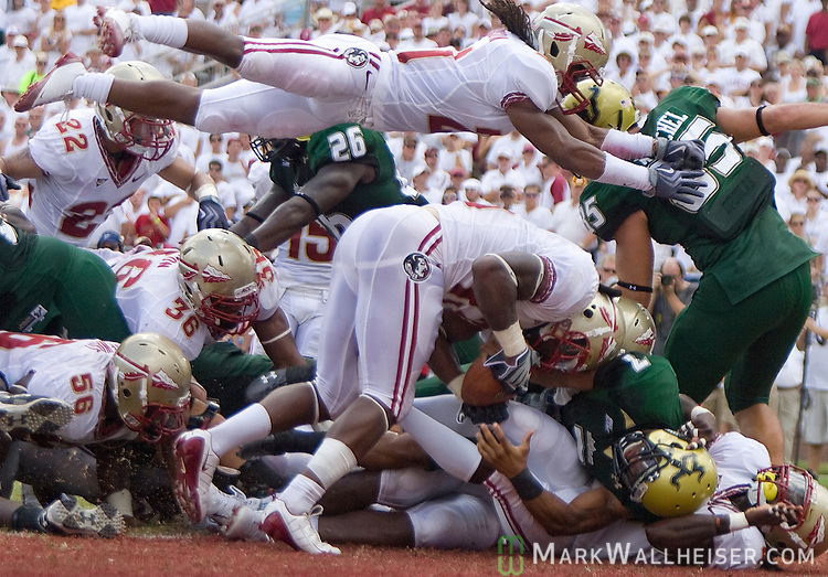 Patrick Robinson, top, takes a flying leap over a defensive pile in the end zone while another Seminole defender tries to take the ball away from USF quarterback B.J. Daniels in the first half of the NCAA football game between the Florida State Seminoles and the University of South Florida Bulls in Tallahassee, Florida September 26, 2009