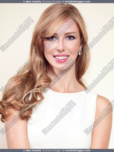 Portrait of a smiling caucasian woman with long blond hair in her thirties isolated on light background