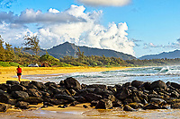 A jogger on the beach at Kawailoa Bay heads toward the Sleeping Giant (or Nounou Mountain), eastern Kaua'i.