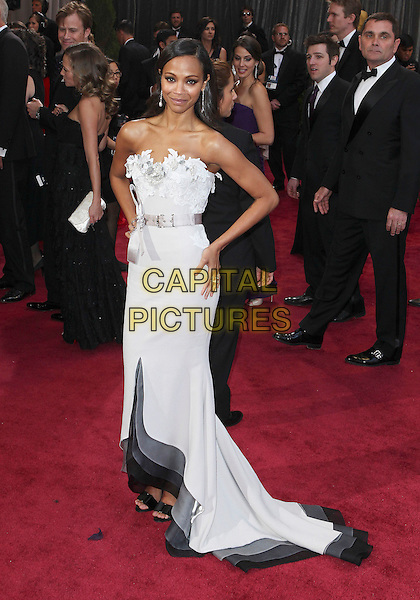 Zoe Saldana (wearing Alexis Mabille Couture).85th Annual Academy Awards held at the Dolby Theatre at Hollywood & Highland Center, Hollywood, California, USA..February 24th, 2013.oscars full length black white grey gray dress hands on hips petal detail bodice ribbon strapless  .CAP/ADM/SLP/COL.©Colin/StarlitePics/AdMedia/Capital Pictures