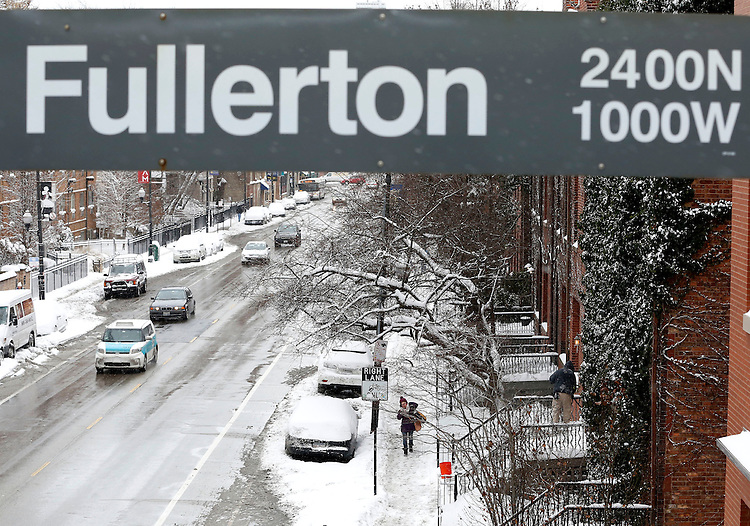 Pedestrians make their way down Fullerton Ave near the Lincoln Park campus of DePaul University in Chicago as the New Year brought two days of lake effect snow and ice. (Photo by Jamie Moncrief)