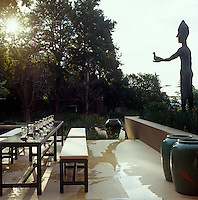 On the terrace of this garden in Johannesburg a long table with matching benches seats up to eighteen watched over by a sculpture of a man with a bird