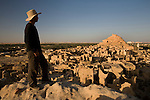 A man in his early 30's, stands on top of the 13th century mud-brick fortress of Shali, at sunrise, in Siwa Town of the Siwa Oasis, near the Libyan border in Egypt.