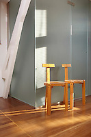 Two simple wooden chairs are set against a grey wall.