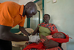 Nurse Atulu George Adam vaccinates a young patient in the Mother of Mercy Hospital in Gidel, a village in the Nuba Mountains of Sudan. The area is controlled by the Sudan People's Liberation Movement-North, and frequently attacked by the military of Sudan. The Catholic hospital is the only referral hospital in the war-torn area.<br /> <br /> Adam is a 2015 graduate of the Catholic Health Training Institute, a school in Wau, South Sudan, sponsored by Solidarity with South Sudan.