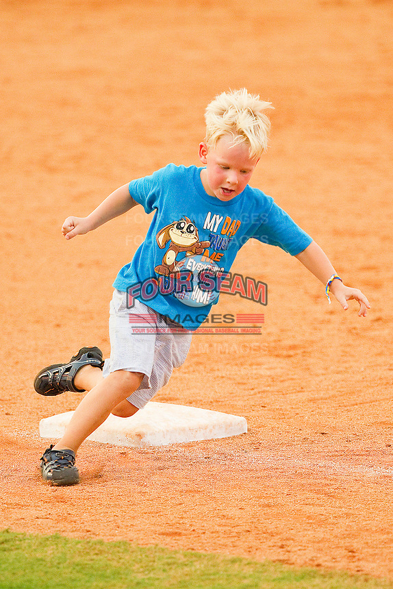A young fan rounds third base as he gets to run the bases following the South Atlantic League game between the Delmarva Shorebirds and the Kannapolis Intimidators at Fieldcrest Cannon Stadium on August 7, 2011 in Kannapolis, North Carolina.  The Intimidators defeated the Shorebirds 8-3.   (Brian Westerholt / Four Seam Images)