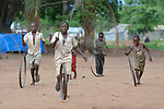 Boys roll wheels through a camp for more than 5,000 displaced people in Riimenze, in South Sudan's Gbudwe State, what was formerly Western Equatoria. Families here were displaced at the beginning of 2017, as fighting between government soldiers and rebels escalated.<br /> <br /> Two Catholic groups, Caritas Austria and Solidarity with South Sudan, have played key roles in assuring that the displaced families here have food, shelter and water.<br /> The camp formed around the Catholic Church in Riimenze as people fled violence in nearby villages for what they perceived as the safety offered by the church.