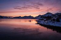 Colorful winter sunset over calm water of Offersøystraumen, near Leknes, Vestvågøy, Lofoten Islands, Norway