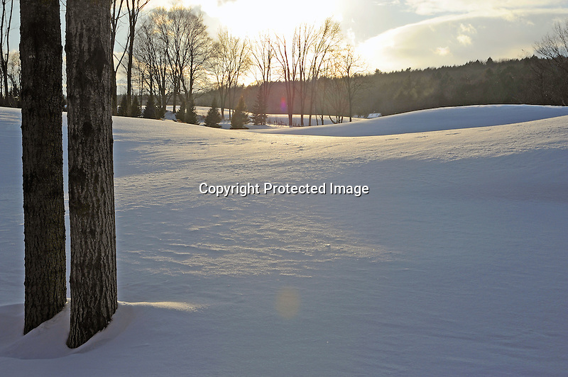 Vermont Farm Nestled in the Snow Covered Hills in Afternoon Sunlight
