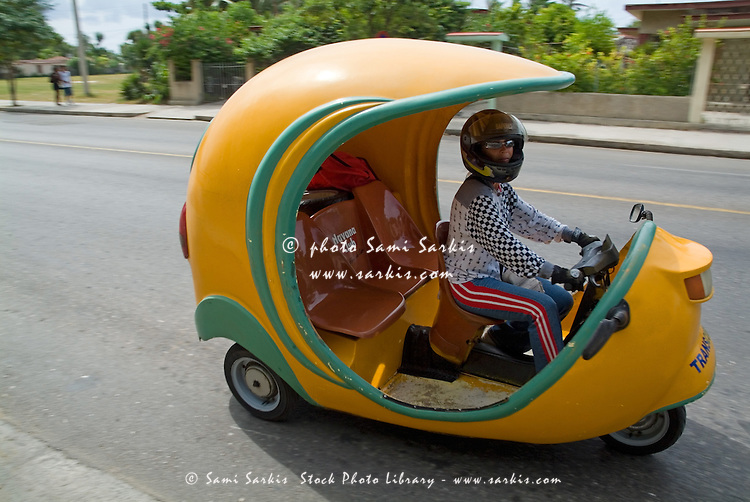 A speeding motorcycle taxi in the streets of Varadero, Matanzas, Cuba.