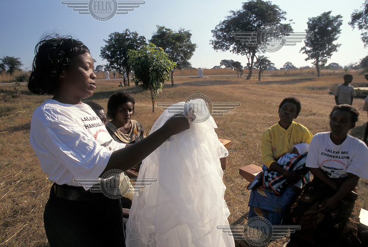 Training session for health workers - demonstration of mosquito nets and malaria prevention education.
