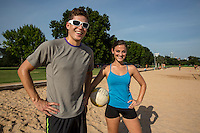Young happy fit athletic couple with volleyball poses at the lush green Zilker Park volleyball courts