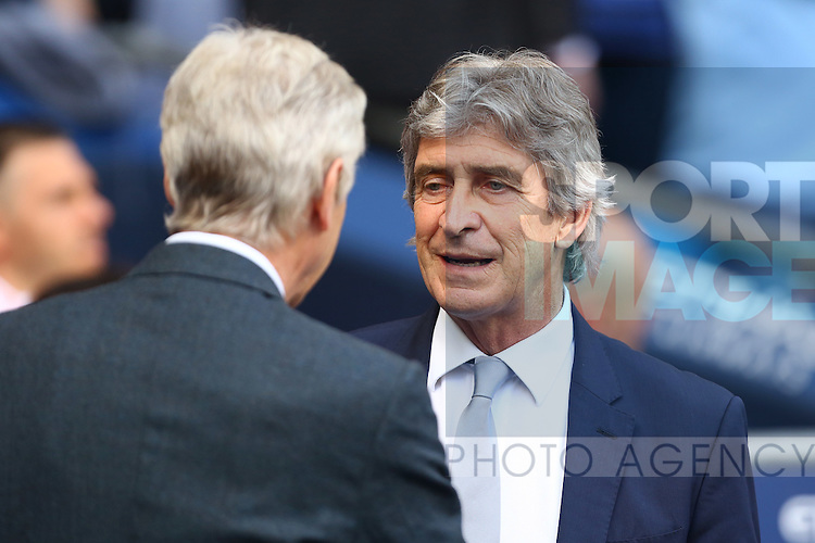 Manuel Pellegrini, manager of Manchester City greets Arsenal's manager, Arsene Wenger during the Barclays Premier League match at the Etihad Stadium. Photo credit should read: Philip Oldham/Sportimage