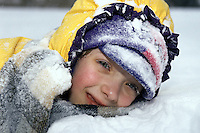Little girl in snow. Girl covered in snow.