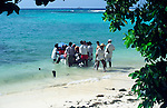 Group of people buying fish from a fishing boat on the beach at La Digue, Seychelles